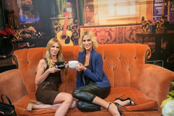 The Real Housewives of New York City's Carole Radziwill (left) and Kristin Taekman celebrate the 20th anniversary of Warner Bros. Television's Friends on the show's iconic orange couch at the Central Perk pop-up replica in New York. (©2014 WBEI. All Rights Reserved.)