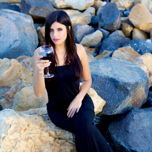 Sensual beauty with black hair and green eyes holding glass of wine