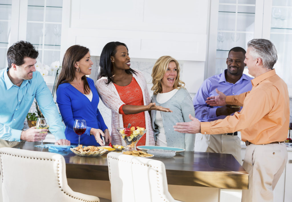 A multi-ethnic group of six adult friends, in their 30s and 40s, having fun at a party in the kitchen of a home or apartment, with wine and appetizers.  They are facing and talking to a man in an orange shirt with his arms outstretched, reaching out to greet them.