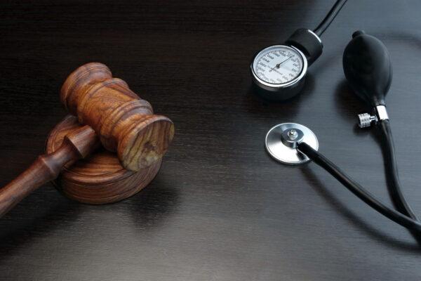 Judges Gavel And Medical Equipment On Black Wooden Background