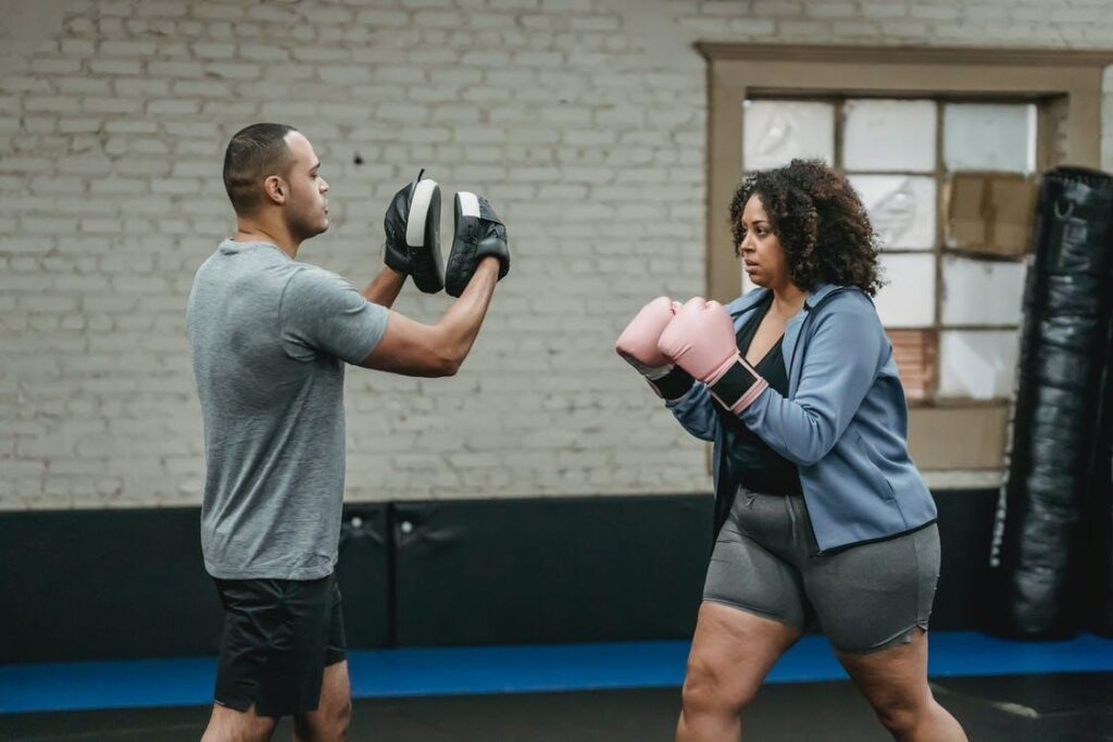 Side view of ethnic trainer explaining technique of punch for concentrated overweight African American woman in boxing gloves during boxing workout